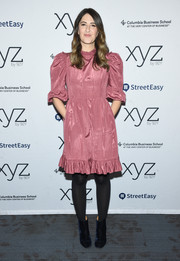 D'Arcy Carden styled her dress with a pair of navy velvet ankle boots.