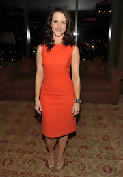 Kristin wears a vibrant orange-red cocktail dress with subtle style lines at the Tory Burch celebration.