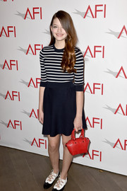 For a pop of color to her dark outfit, Mackenzie Foy accessorized with a red leather purse.