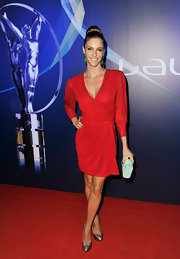 Fernanda Lima opted for a red cocktail dress with long sleeves and a gathered waist for a sleek and sophisticated red carpet look.