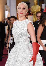 Lady Gaga attended the Oscars looking uncharacteristically tame in a conservative white dress. She did, however, punch it up with a pair of red leather gloves. Now that's the Gaga we know!