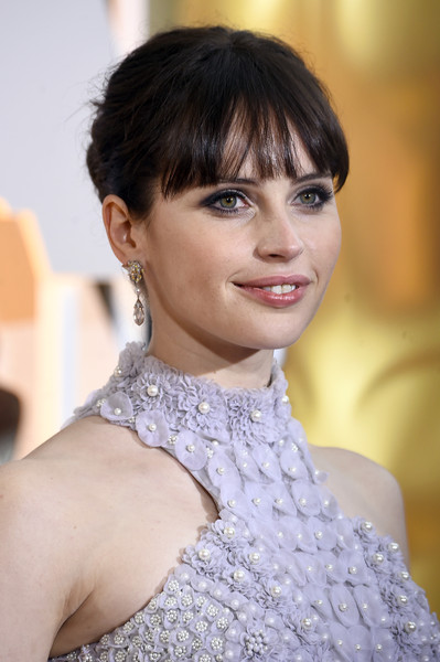 Felicity Jones opted for a classic bun with youthful blunt bangs when she attended the Oscars.