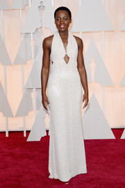 Lupita Nyong'o radiated on the Oscars red carpet in a pearl-embellished white Calvin Klein gown, made sexier with the addition of center and side cutouts.
