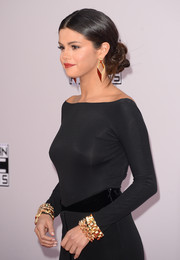 Selena Gomez styled her black dress with layers of chunky gold bracelets for the American Music Awards.