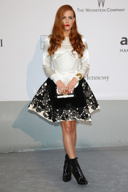 Riley Keough completed her ensemble with a trendy black-and-white Louis Vuitton box clutch.
