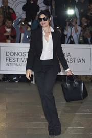 Monica Bellucci styled her outfit with a studded black leather tote.