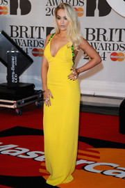 Rita Ora looked oh-so-hot at the Brit Awards in a rhinestone-embellished yellow Prada gown with a plunging neckline.