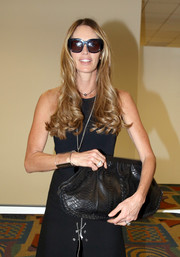 Elle MacPherson accessorized with an oversized black snakeskin clutch during day one of Art Basel Miami Beach.