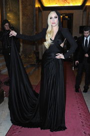 Lady Gaga looked absolutely divine in a hooded black cutout gown by Atelier Versace when she attended the label's fashion show.