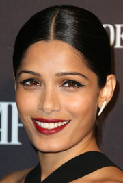 Freida Pinto kept it classic with this sleek center-parted bun at the Audemars Piguet Rodeo Drive grand opening.