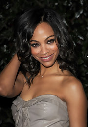 Zoe Saldana styled her shoulder length tresses in soft medium curls. A subtle side part provided the perfect frame for her face.