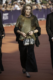 Catherine Deneuve finished off her outfit with black bell-bottoms.