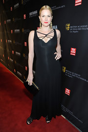Alice Evans wore a black floor-length evening dress with a unique woven neckline for the BAFTA Britannia Awards.