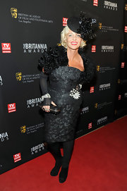 Amanda Eliasch wore an elaborate ensemble consisting of an embroidered LBD, shoulder shrug, sheer gloves and opaque tights.