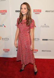 Alicia Vikander went for a simple red and white striped midi dress that she complemented with pointed black heels.
