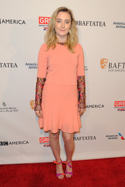 Saoirse Ronan brightened up the room in a coral above-the-knee dress with embroidered sleeve details. The actress finished her look with mutlicolored purple and orange heels.