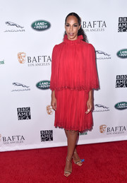 Amanda Brugel chose a red cocktail dress with a ruffled neckline and a layered bodice for the BAFTA Los Angeles + BBC America TV Tea Party.