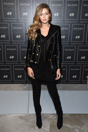 Gigi Hadid layered a gold-buttoned leather jacket over a little black dress, both by Balmain x H&M, for the collaboration's launch.