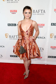 Maisie Williams tied her look together with a metallic-gold pyramid purse.