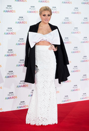 Pixie Lott tamed that huge bow with a black coat as she posed on the BBC Music Awards red carpet.