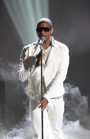Usher wears a crinkled white leather jacket as part of his all white ensemble for his performance at the BET awards.  With a studded mandarin collar and open front, this sleek fitting number is quite original.