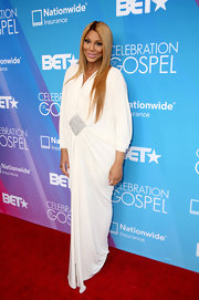 Tamar Braxton sported a long and flowing evening dress with crystal embellishments on the stomach.