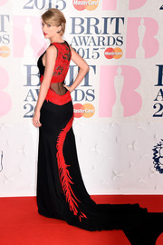 Taylor Swift went for a dramatic look for the BRIT Awards in a red and black gown complete with mesh inserts and a long train.