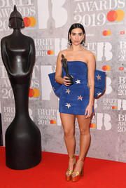 Dua Lipa styled her frock with towering gold platforms, also by Saint Laurent.