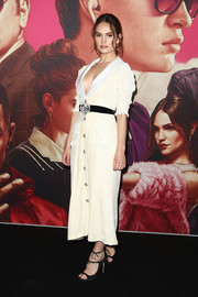 Lily James chose a pair of black triple-strap sandals by Jimmy Choo to complete her outfit.