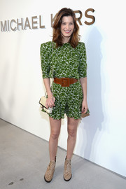 Hanneli Mustaparta cinched her romper with an oversized brown leather belt.