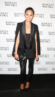 Chrissy Teigen looked fiercely stylish in a black blazer cape with satin lapels during the Badgley Mischka fashion show.