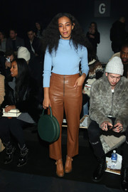 Solange Knowles added an extra pop of color with a round green tote by Furla.
