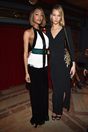 Karlie Kloss sheathed her slim physique in a black wrap gown with gold leaf detailing for the Balmain aftershow dinner.