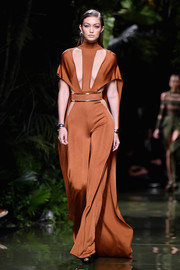 Gigi Hadid looked foxy on the Balmain runway in a caped jumpsuit with cleavage-baring cutouts.