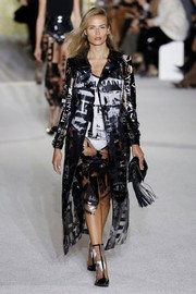 Natasha Poly looked uber cool in a graphic PVC coat layered over a matching dress at the Balmain runway show.