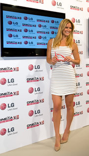 Bar Refaeli shows off her curves in a white striped bandage dress for her TV appearance in Barcelona.