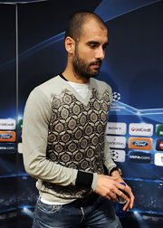 Josep wears a gray v-neck sweater with a graphic design and black cuff sleeves.