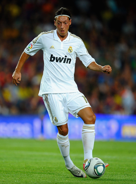 Mesut Ozil uses a white headband to keep his long hair away from his face and eyes.