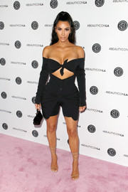 Kim Kardashian flashed plenty of skin in a Dolce & Gabbana off-the-shoulder top with a midriff cutout, which she teamed with bike shorts, at the Beautycon Festival LA 2018.