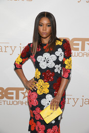 Gabrielle Union paired a yellow leather clutch with a floral-sequined frock for a festive, colorful look during the premiere of 'Being Mary Jane.'