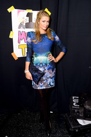 Paris Hilton added sparkle to her ensemble with a sequined blue clutch.