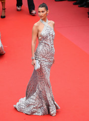 Bella Hadid complemented her dress with a gray Judith Leiber clutch.