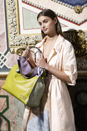 Taylor Hill showed off her personalized leather tote while waiting backstage at the Bottega Veneta show.