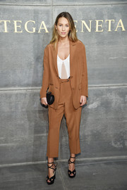 Dylan Penn attended the Bottega Veneta fashion show wearing a cropped tan suit from the brand.
