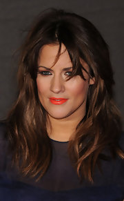 Carline Flack made her olive skin glow with a bright lip color with a slight orange tint to it.