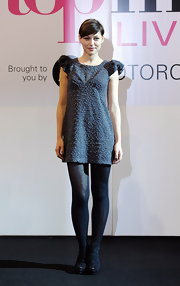 Emma wears a textured gray dress with exaggerated shoulder poufs.