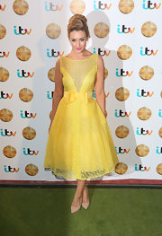 Catherine Tyldesley chose a retro-style lace frock with a full skirt and matching yellow belt for her fun and flirty evening look.