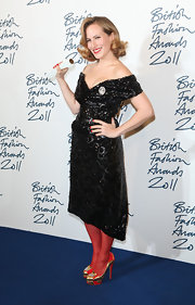 Charlotte Dellal wore a shining black off-the-shoulder cocktail dress with sheer red tights to receive her award at the BFAs.