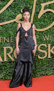 FKA Twigs worked a deconstructed look in a black split-seam dress by Calvin Klein at the British Fashion Awards.