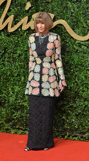 Anna Wintour looked regal in a beaded floral coat layered over a black column dress at the British Fashion Awards.